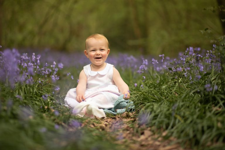 Smiling toddler in bluebells with teddy Bluebell photoshoot in Sussex family photographer Haywards Heath
