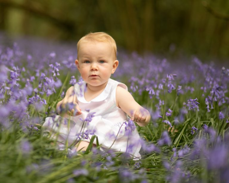 little girl Sat in the bluebells during photoshoot family photographer Haywards Heath