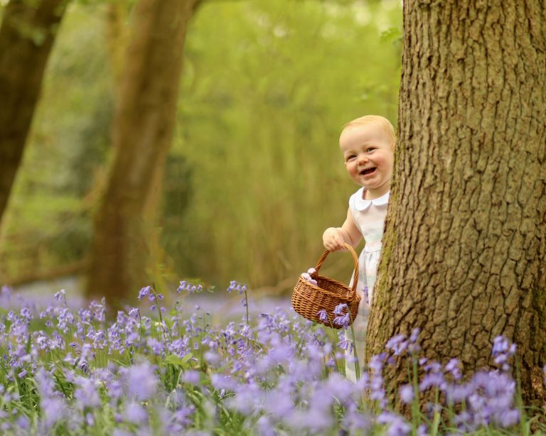 Little girl peeking from behind tree in Sat in the bluebells during photoshoot family photographer Haywards Heath