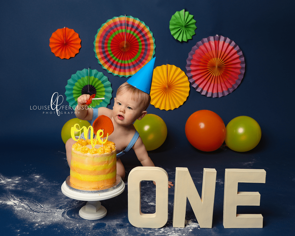 Blue colourful backdrop with primary colour decorations and balloons. Baby boy with blue party hat looking at his 1st birthday cake during cakesmash photoshoot in Glasgow