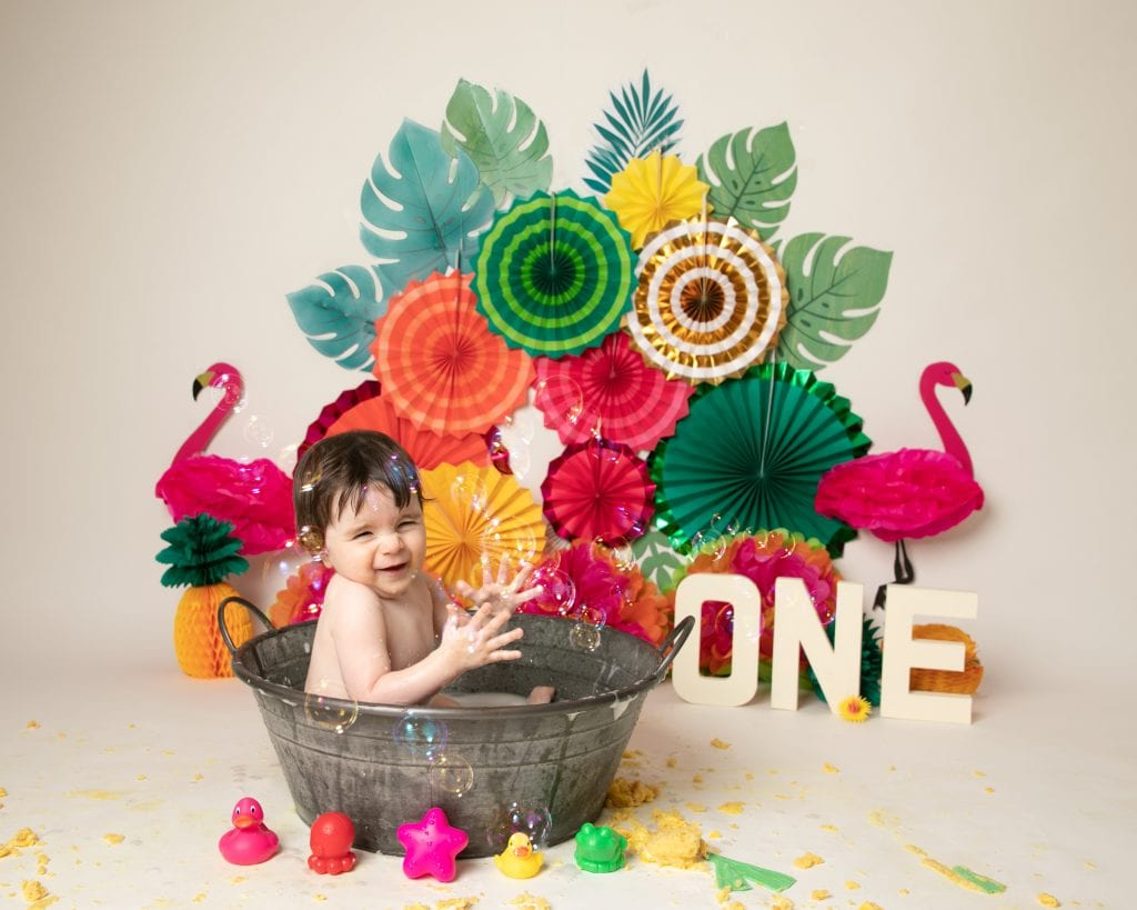 Tropical backdrop brightly coloured with baby girl sat in tin bath splashing at 1st birthday cakesmash photoshoot in Glasgow