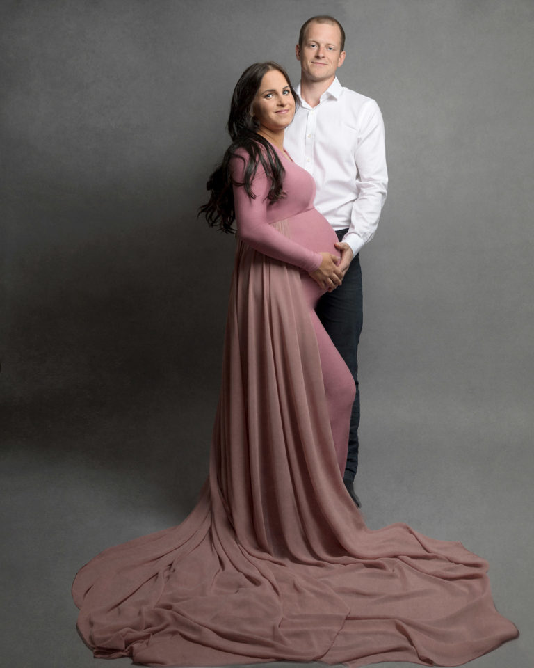 Pregnant mum wearing maternity gown with dad in pregnancy photoshoot