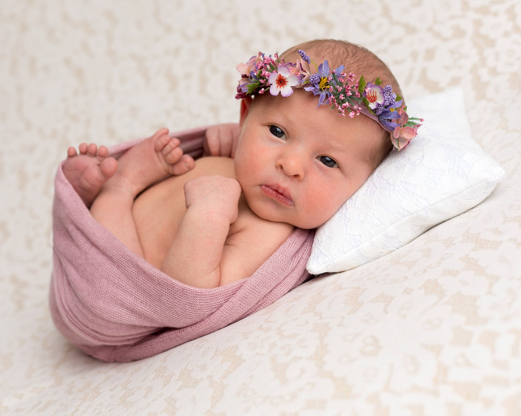 Newborn photoshoot baby girl in pink on lace blanket