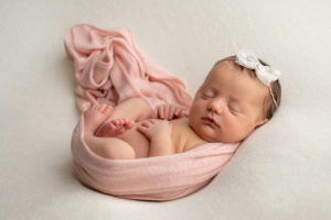 Baby in peach wrap by haywards heath photographer