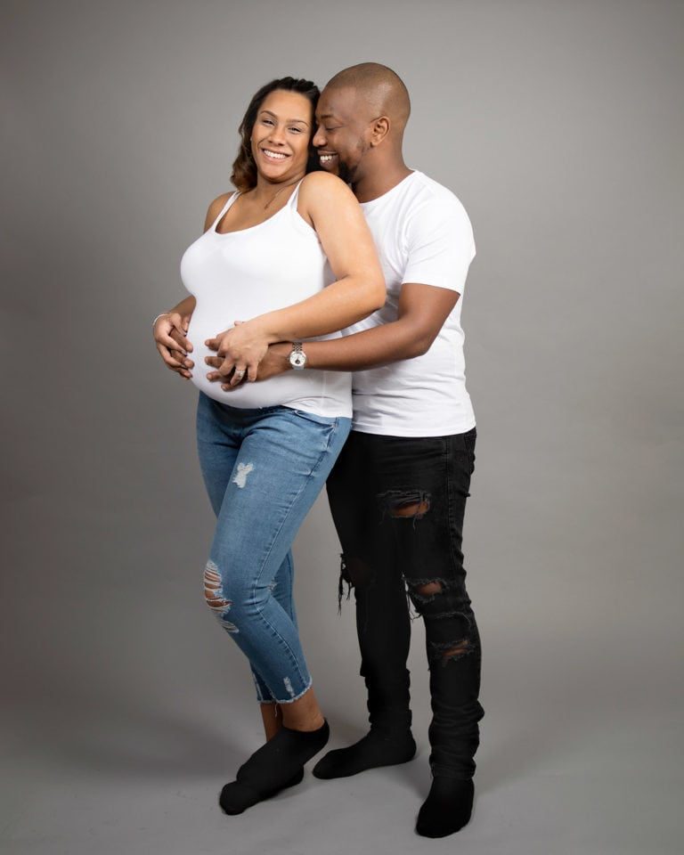 Patents cuddling in casual dress during pregnancy photoshoot