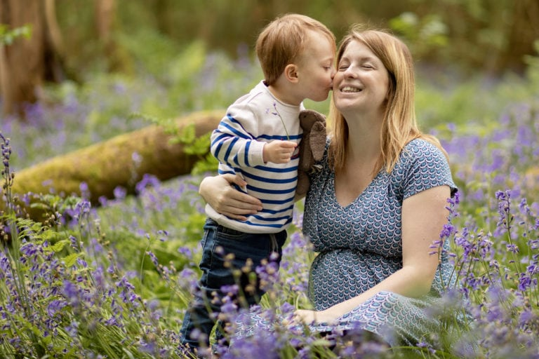 Little boy kissing pregnant mum in bluebells.Family photographer haywards heath