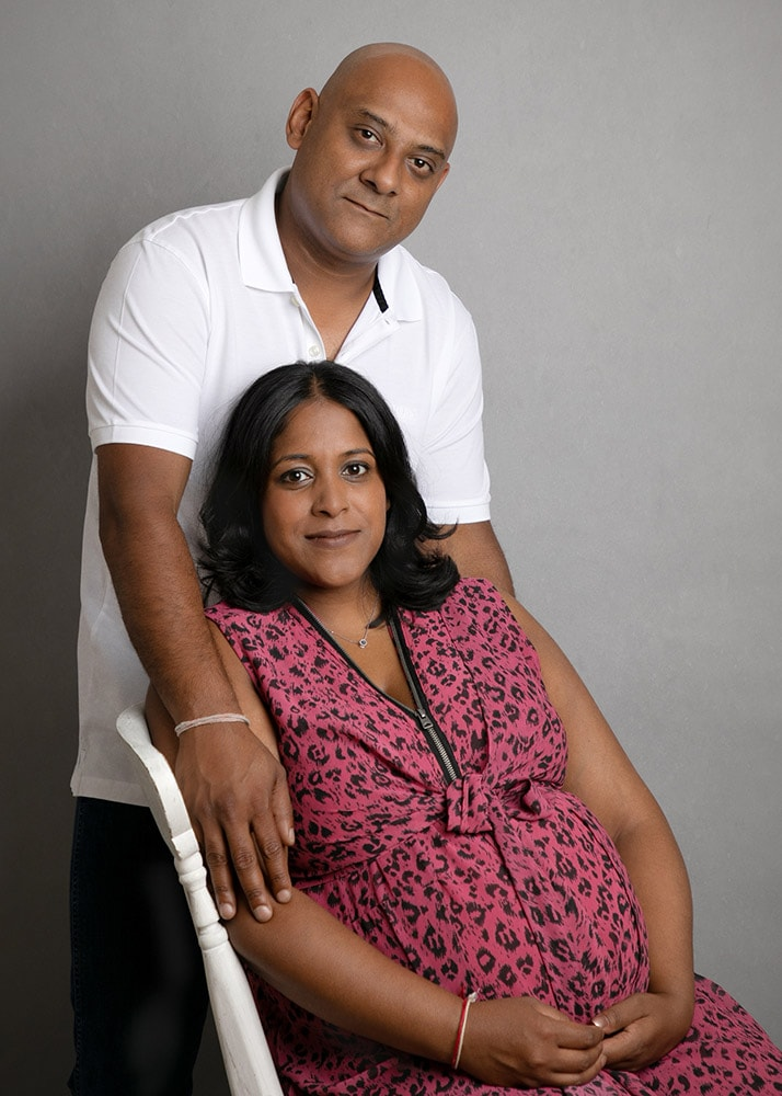 Pregnant mummy sat with hubby in pregnancy photoshoot in Haywards Heath
