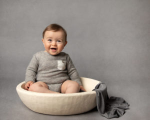 Baby in cream bowl wearing grey romper with Glasgow baby photographer