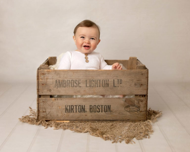 Baby in wooden crate during baby photography session