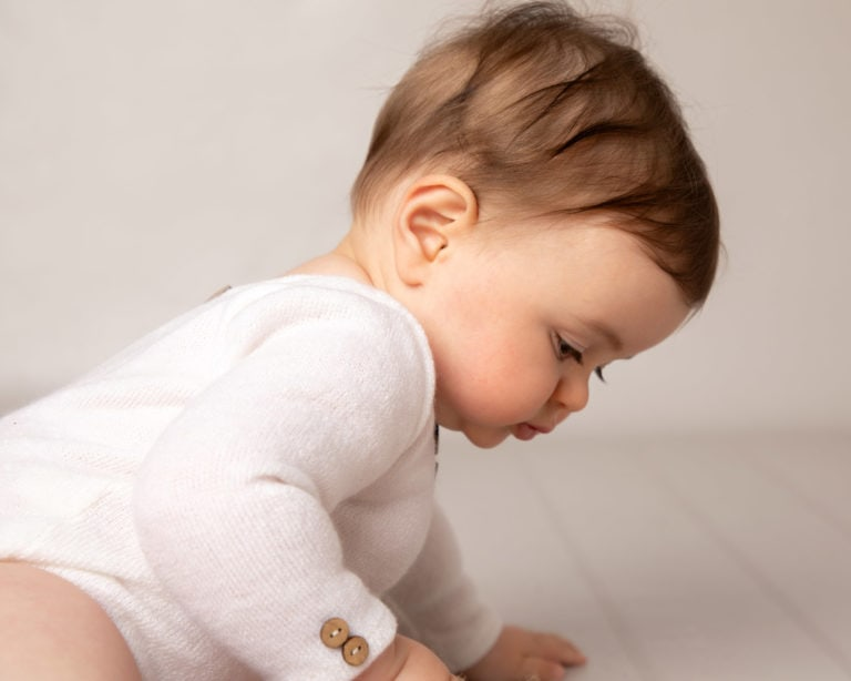 side profile of baby wearing white romper during baby photography session
