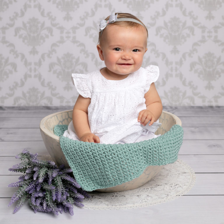 Older baby girl sat in bowl during baby photography session