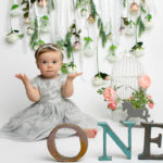 Baby photoshoot cakesmash session, floral backdrop with pastel tones girl in silver dress in Haywards Heath