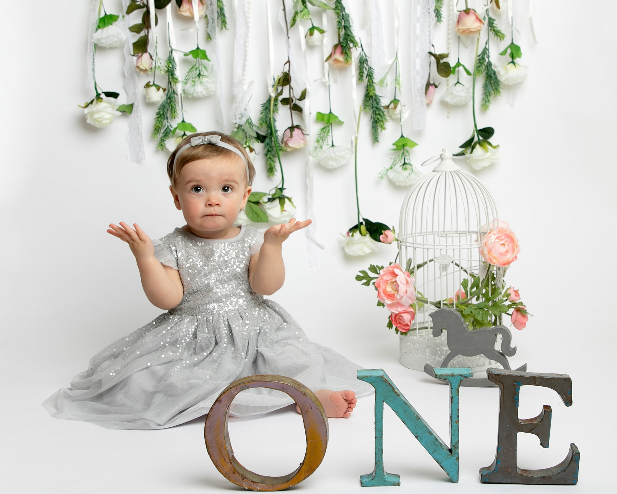 1st Birthday Cakesmash photoshoot cakesmash session, floral backdrop with pastel tones girl in silver dress with Glasgow photographer