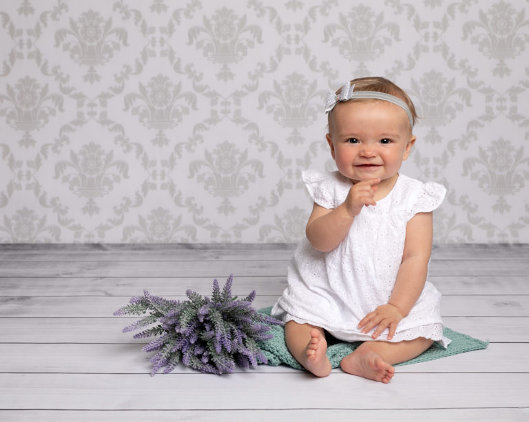 Baby girl sat on grey floor in baby photography session in Horsham by Louise Baby Photographer