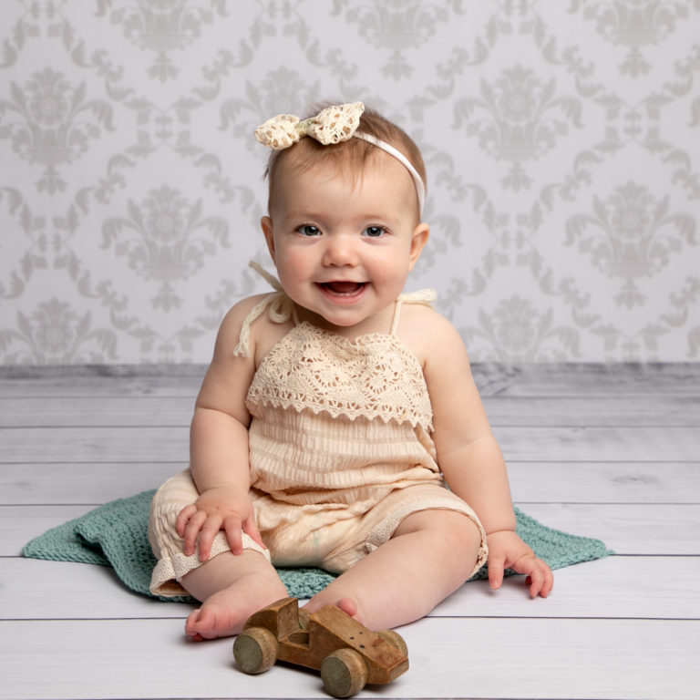 Baby photoshoot, little girl sat on teal blanket at Horsham baby photographers studio