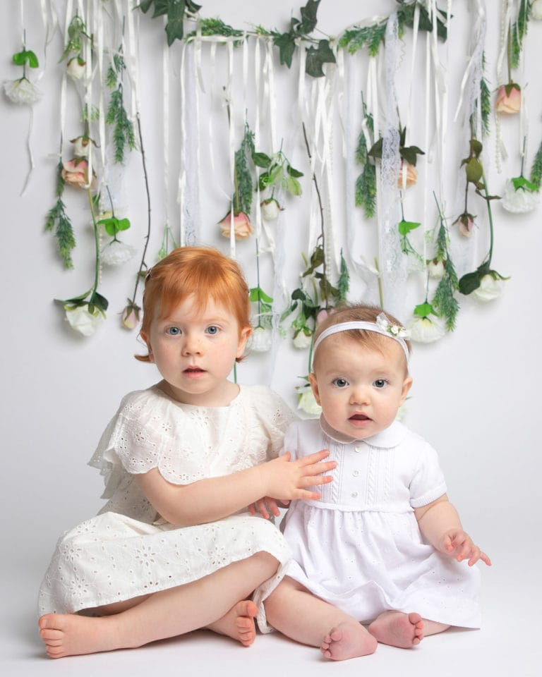 Sisters on floral backdrop during during baby photography session