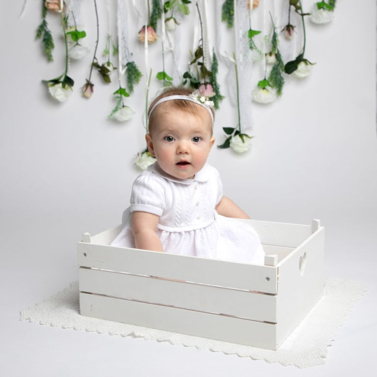 Baby girl in white crate during baby photography session