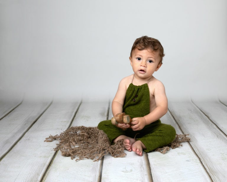 Baby boy in green romper on cream backdrop taken by Horsham baby photographer