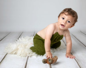 Baby boy playing with car during baby photography session