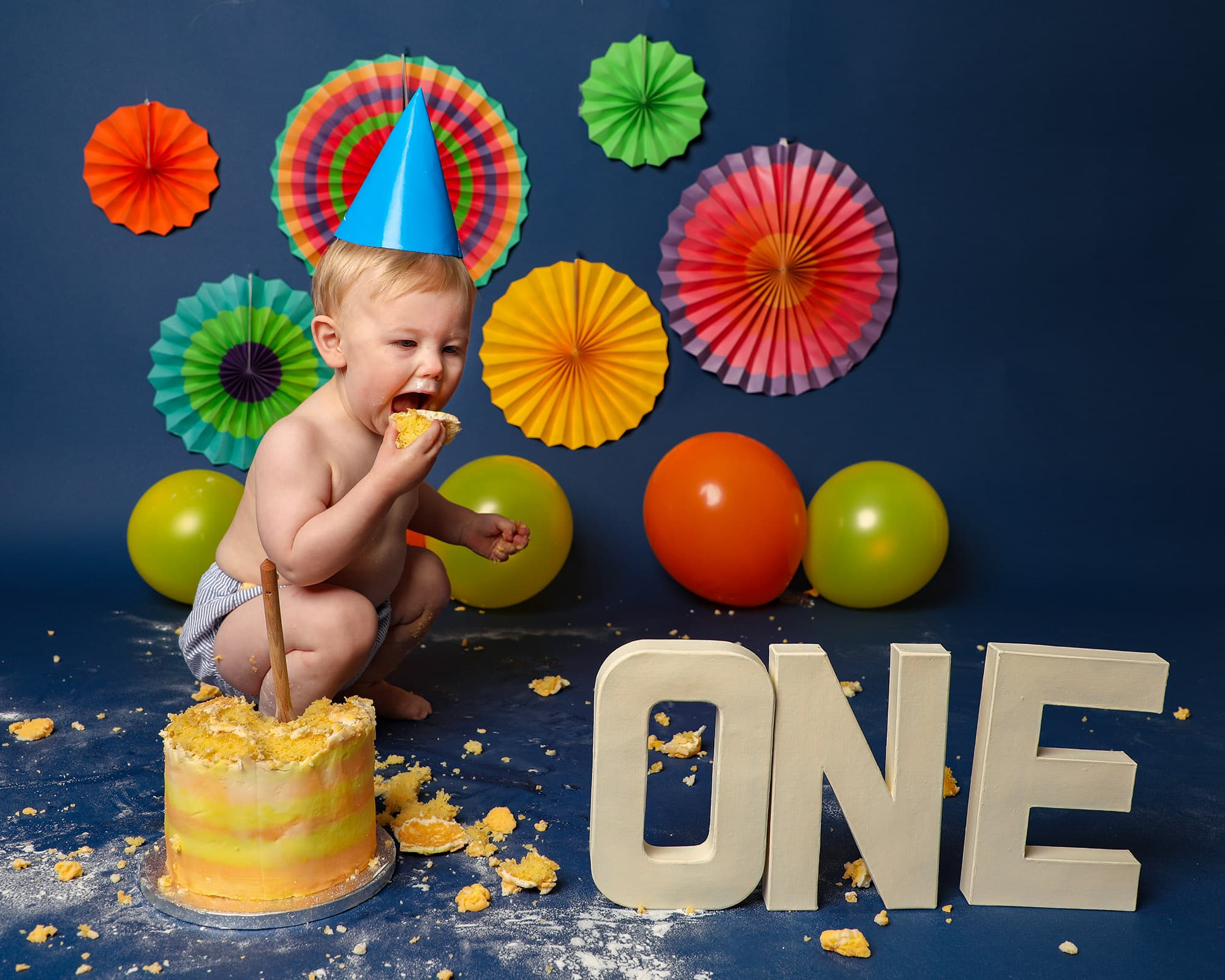 Glasgow studio photoshoot for 1st birthday cakesmash. Baby boy wearing blue party hat eating cake on bright & colourful backdrop of primary colours
