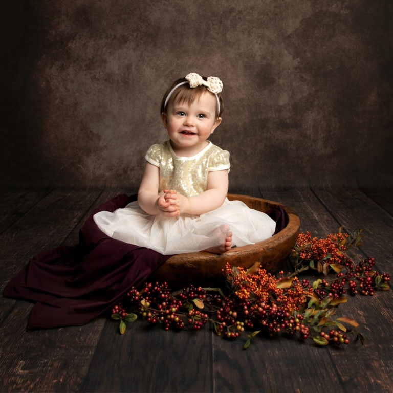 Baby girl in autumnal bowl during baby photography session