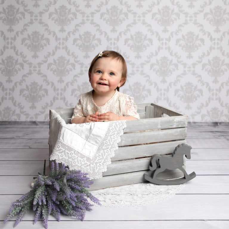 Baby girl in crate in baby photography session