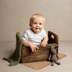 Baby boy in box during baby photography session