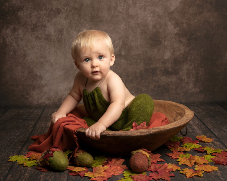 baby photography session baby in bowl with autumnal leaves