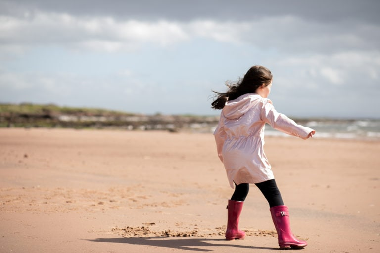 Outdoor family photoshoot, girl playing on beach by haywards heath photographer