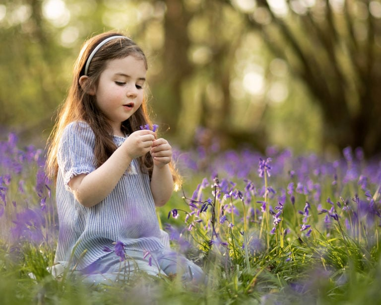 Family photographer Haywards Heath captures girl sat in bluebells playing with flower