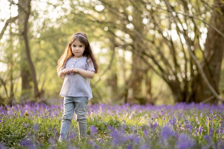 Girl walking in bluebells with family photographer Haywards Heath