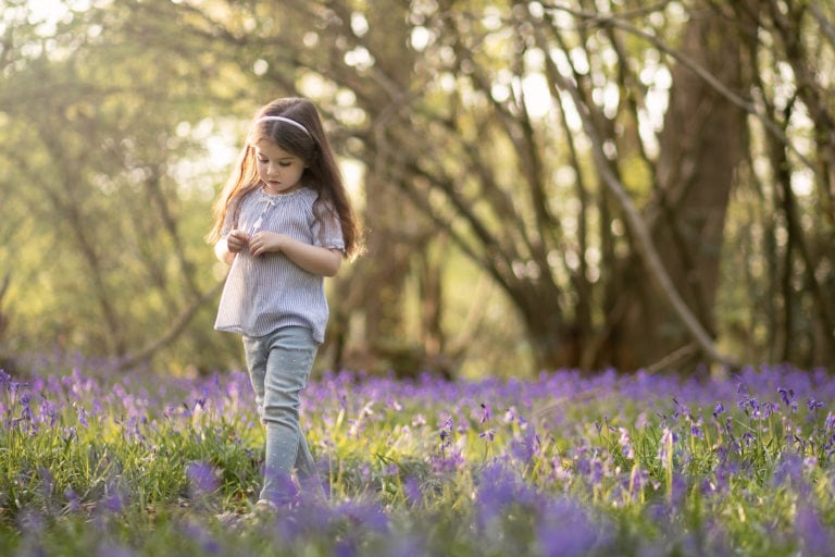 Outdoor family photoshoot, girl in bluebell looking at the flowers family photographer Haywards Heath