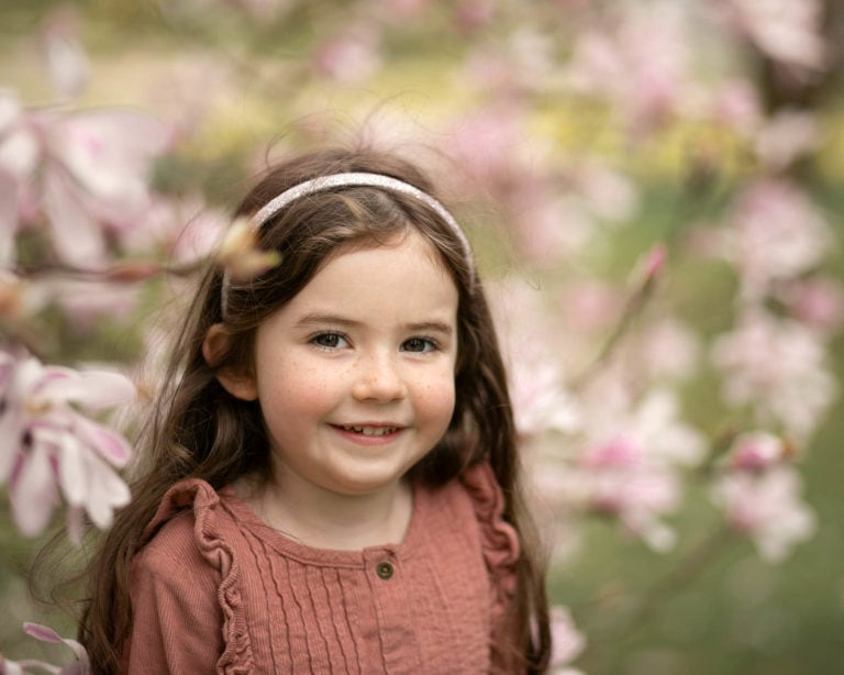 Outdoor family photoshoot in Spring. Girl in front of blossom tree family photographer Haywards Heath