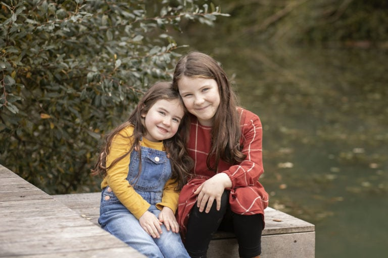 Sisters posing by a lake on a deck during a family photoshoot, by family photographer Haywards Heath