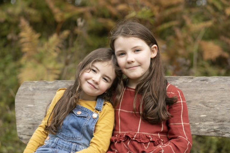 Autumn family photoshoot sisters posing on bench in autumnal colours by family photographer Haywards Heath