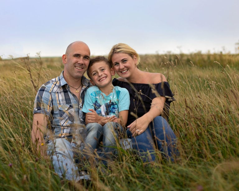 Family sat on hillside at sunset during photoshoot with haywards heath family photographer