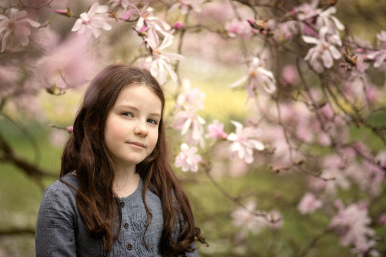 Outdoor family photoshoot in Spring. Girl in front of blossom tree by family photographer Haywards Heath