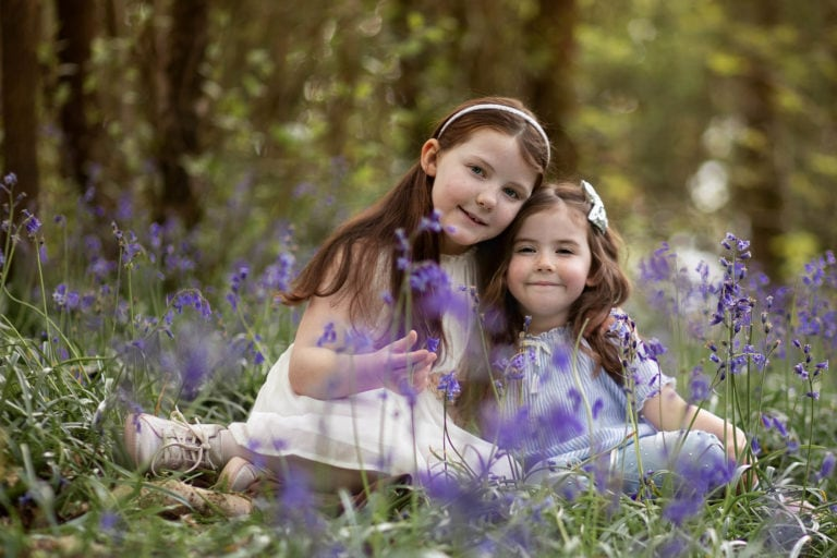 Sister posing sat in bluebelss by family photographer Haywards Heath