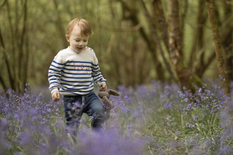 Boy walking in bluebells in Haywards heath by family photographer