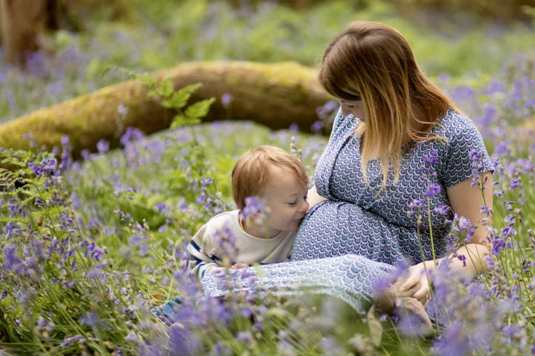 Boy kissing mummy's tummy during bluebell photoshoot by family photographer haywards heath