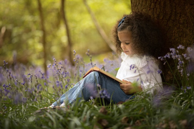 Girl reading book in bluebells by family photographer Haywards Heath