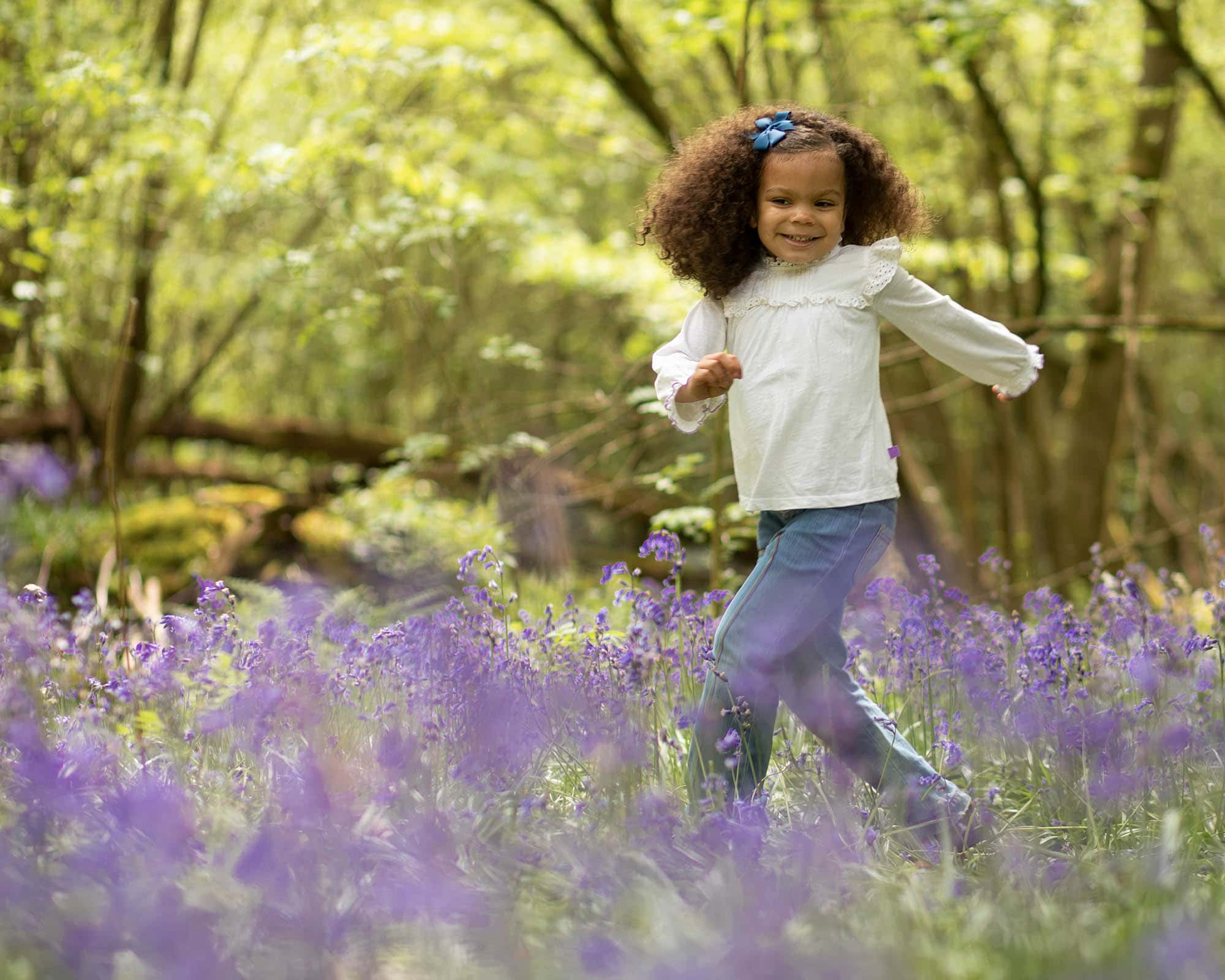 girl running in bluebells as part of a family bluebell photography session in Glasgow