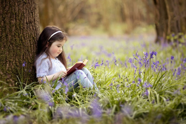 Girl sat in bluebells reading abook up against a tree by family photographer Haywards Heath