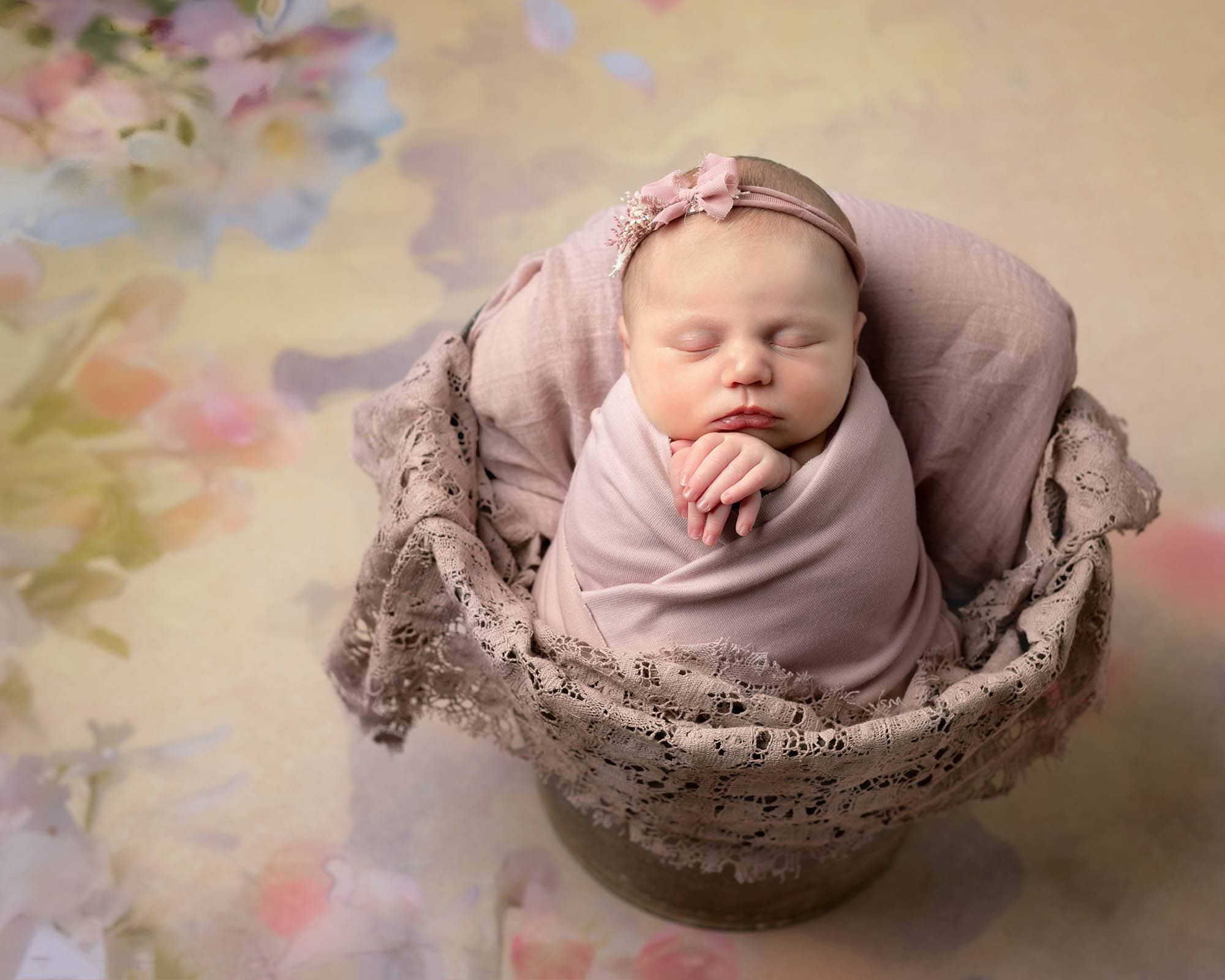 Haywards Heath Photographer posed baby girl in a bucket on floral backdrop