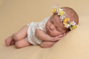 Baby girl photographed by haywards heath photographer wearing lace outift, floral halo on lemon fabric during newborn photoshoot wioth haywards heath photographer