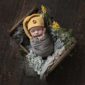 Baby wearing mustard hard in wooden crate by Newborn Photographer in Haywards Heath