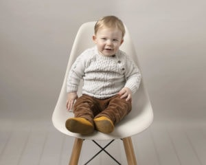 Baby boy sat on a cream hermes chair, wearing brown cord and cream knit jumper. Baby is smiling at his baby photography session with Glasgow photographer