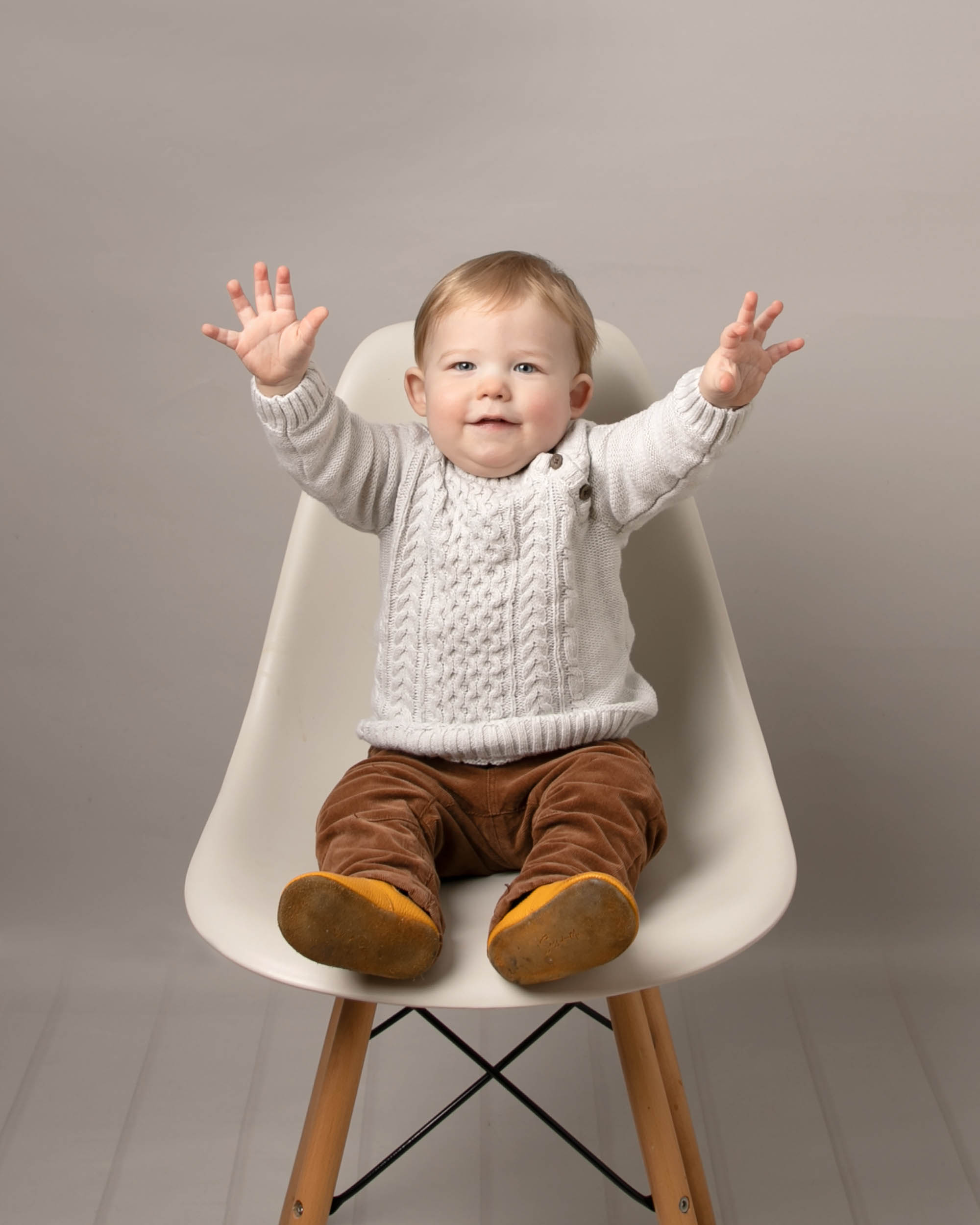 Baby on chair in cream jumper
