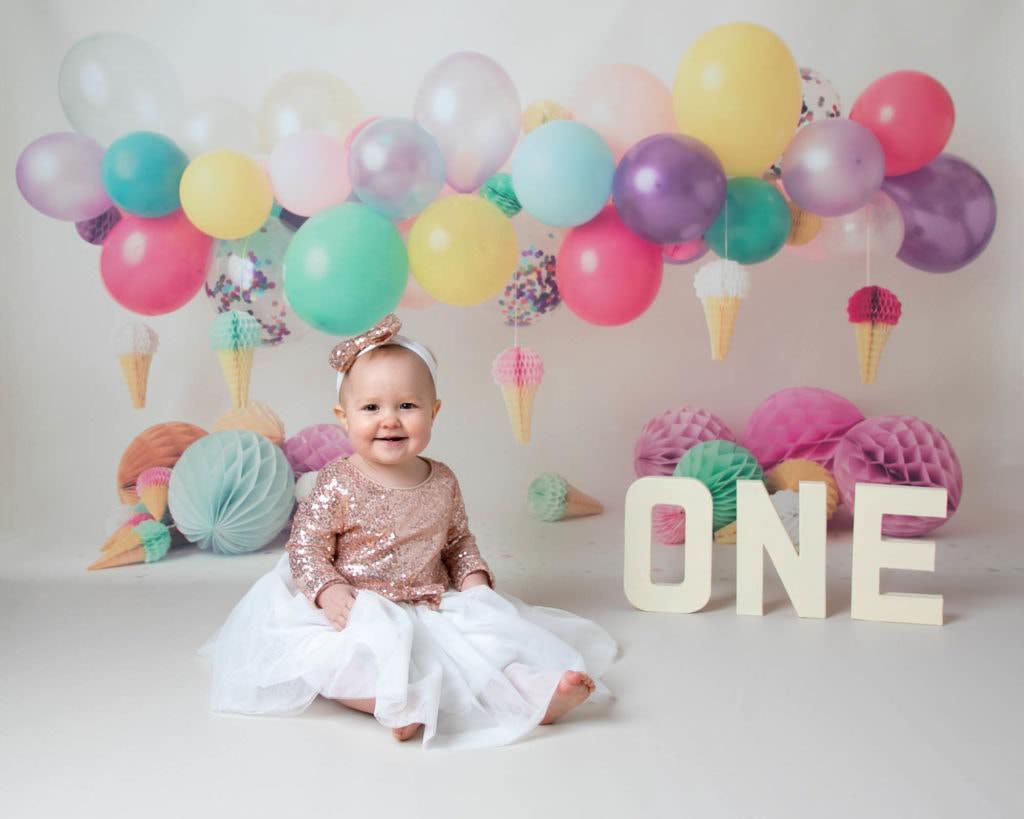 Rainbow balloon backdrop with girl in Glitter dress by1st birthday photoshoot Cakesmash Glasgow baby photographer