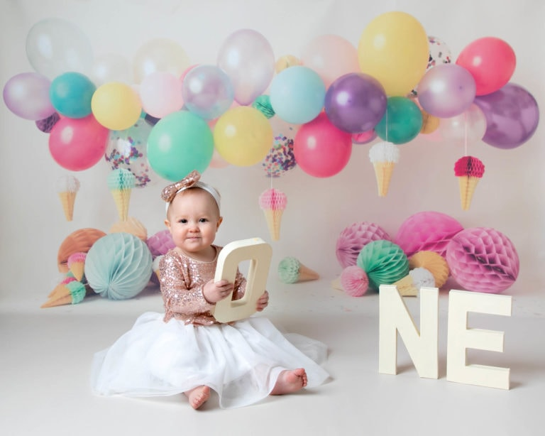 Cakesmash photoshoot baby girl portrait on balloon backdrop wearing pink glittery dress by haywards heath photographer